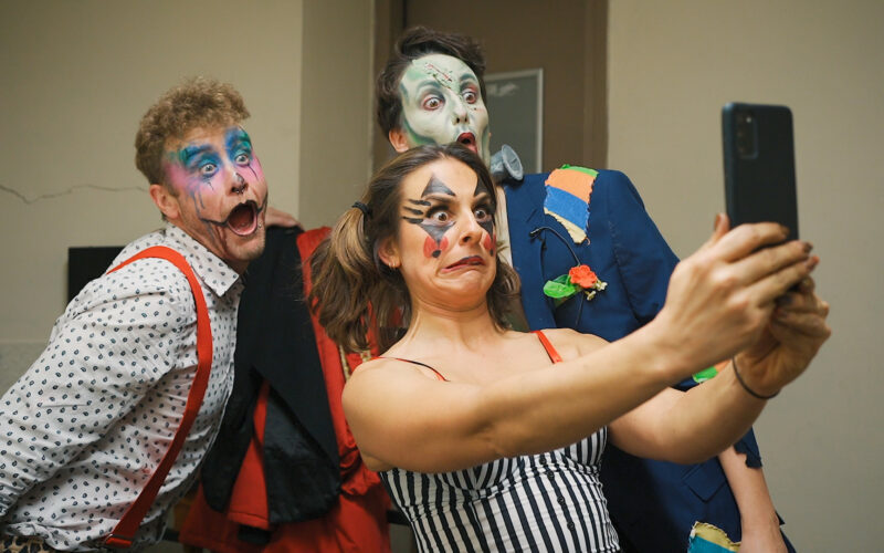 Three performers in stage make up taking a selfie